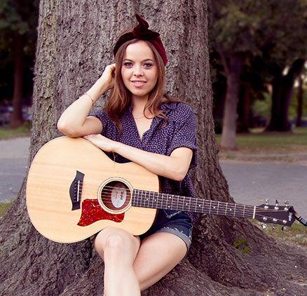 Imagen de Tamara Laurel con su guitarra sentada bajo un árbol